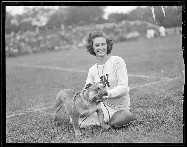 1938: Cheerleader with 'W' on her sweater with bulldog mascot