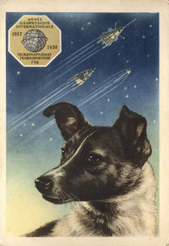 A portrait of Laika by the artist E. Gundobin is seen on a postcard, with the first three Sputniks in the background.