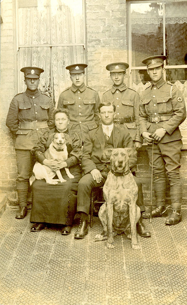 Four soldiers standing behind seated civilians and two dogs, 1st August 1915. From the Left: Soldier (1) Regt unidentified, Soldier (2) Regt Wiltshire Regiment, Soldier (3) Regt Wiltshire Regiment, Soldier (4) Regt Royal Army Medical Corps (RAMC)